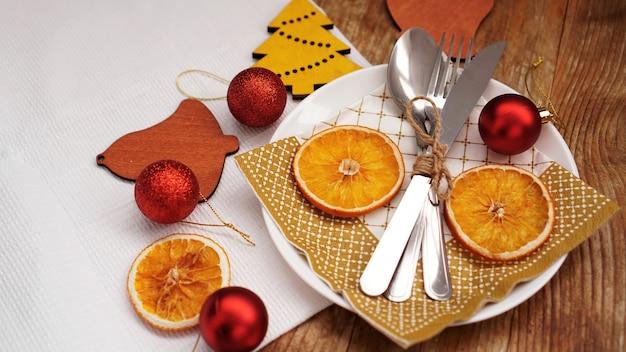Ogólny widok ustawienia świątecznego stołu na drewnianym stole z miejsca na kopię. biały talerz z suszonymi pomarańczami, czerwonymi kulkami i drewnianymi figurkami świątecznymi