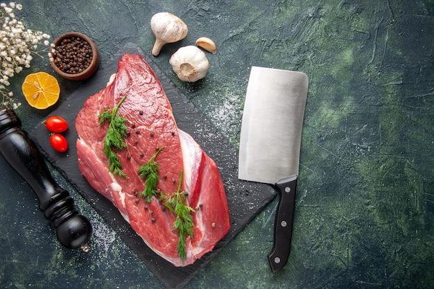 Ogólny widok zieleni na świeżym czerwonym surowym mięsie na desce do krojenia i pieprzu cytryna czarny młotek kwiat na zielonym czarnym mieszanym kolorze tła
