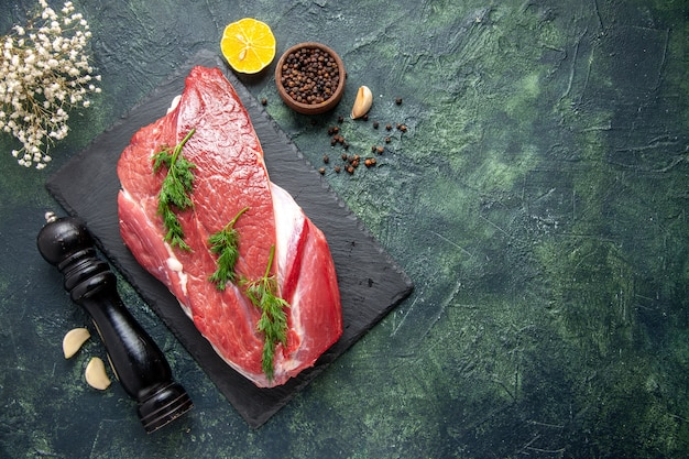 Ogólny widok zieleni na świeżym czerwonym surowym mięsie na desce do krojenia i pieprzu cytryna drewniany młotek po prawej stronie na zielonym czarnym tle mix kolorów