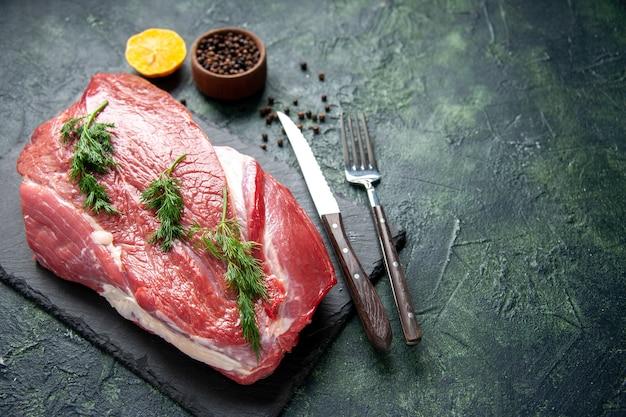 Ogólny widok zieleni na sztućce świeżego czerwonego surowego mięsa na desce do krojenia i cytryny pieprzowej na zielonym czarnym tle mix kolorów