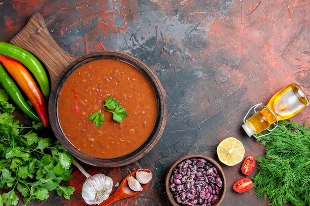 Ogólny widok zupa pomidorowa spadł fasola butelka oleju na deski do krojenia na tabeli kolorów mieszanych