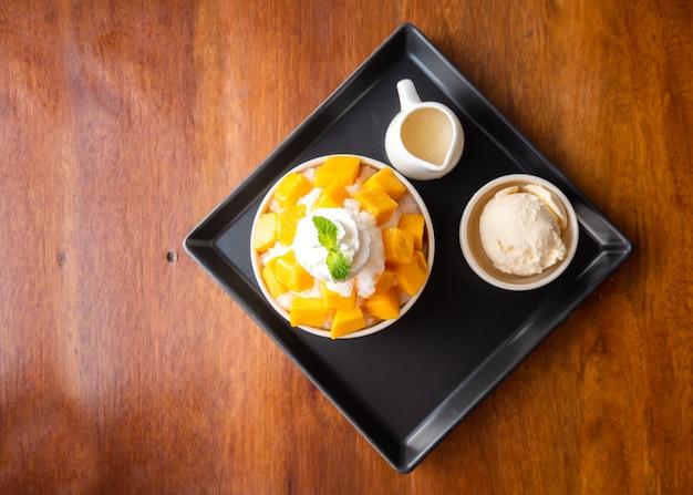 Ogolony deser lodowy z plasterkami mango. podawane z lodami waniliowymi i bitą śmietaną.
