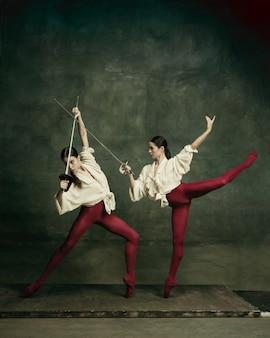 Ogon wróżki. dwie młode tancerki baletowe jak pojedynki z mieczami na ciemnozielonym tle. kaukaski modele tańczą razem. koncepcja baletu i choreografii współczesnej. kreatywne zdjęcie artystyczne.