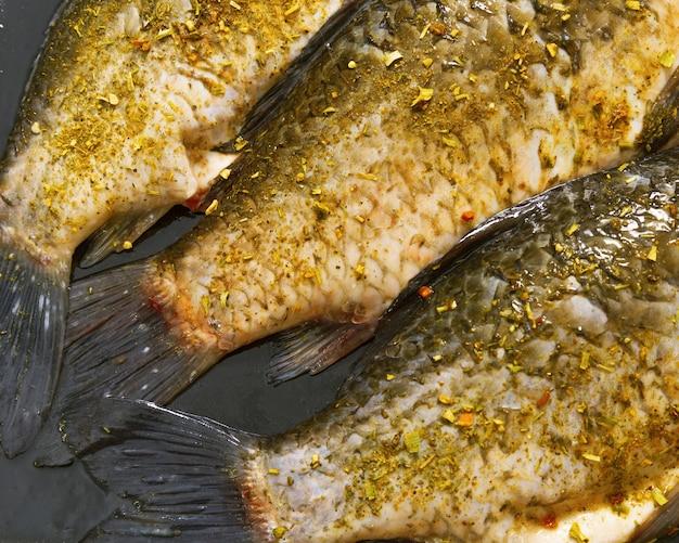Ogony rybne leżące na czarnej patelni przygotowane do pieczenia w piekarniku