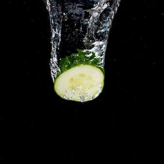 Ogórek z wodnym pluśnięciem spada na czarnym tle