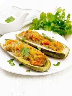 Ogórki faszerowane mięsem mielonym, pomidorami, papryką z serem i natką pietruszki w talerzu, sos śmietanowo-zieleniny w łódce, ręcznik na tle drewnianej deski