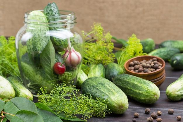 Ogórki, główka czosnku i wiśni w szklanym słoju. ogórki, koperek i ziele angielskie w drewnianej misce na stole. domowe produkty fermentacyjne. drewniane tło. widok z góry.