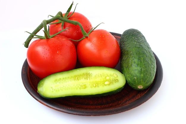 Ogórki i pomidory na talerzu na białym tle