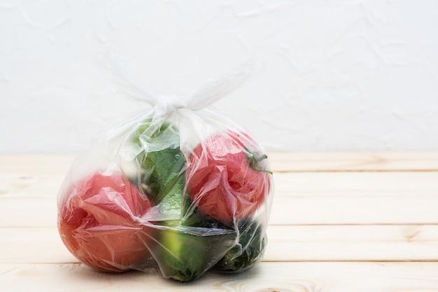Ogórki i pomidory pakowane są w jednorazową plastikową torbę na drewnianym stole