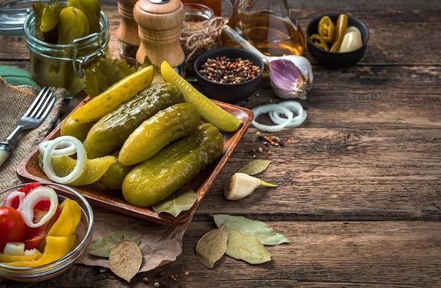 Ogórki kiszone, czosnek i liść laurowy na tle drewnianych. pojęcie tła kulinarnego.