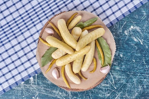 Ogórki kiszone, czosnek, papryka i liść na drewnianym talerzu z obrusem.