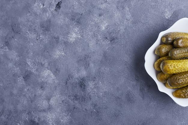 Ogórki kiszone na białym talerzu na niebieskim tle.
