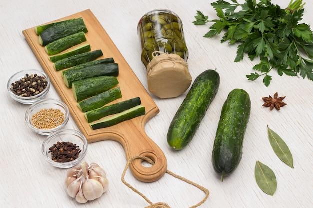 Ogórki konserwowe, ogórki krojone na desce do krojenia, pietruszka zielona, czosnek i przyprawy. domowe produkty fermentacji. zdrowe odżywianie zimowe. biała powierzchnia. widok z góry.