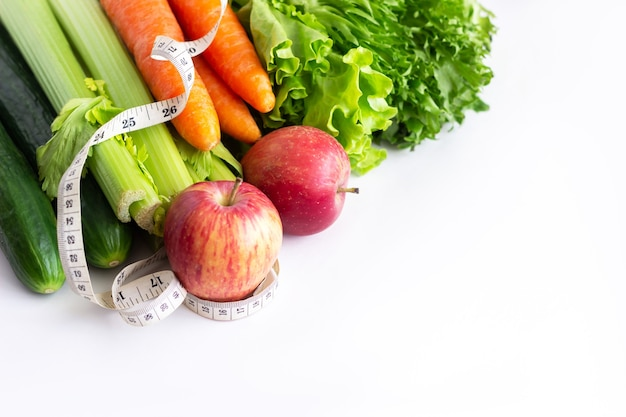 Ogórki, seler, marchew, zielona sałata, czerwone jabłka i taśma miernicza na białym tle na białej ścianie