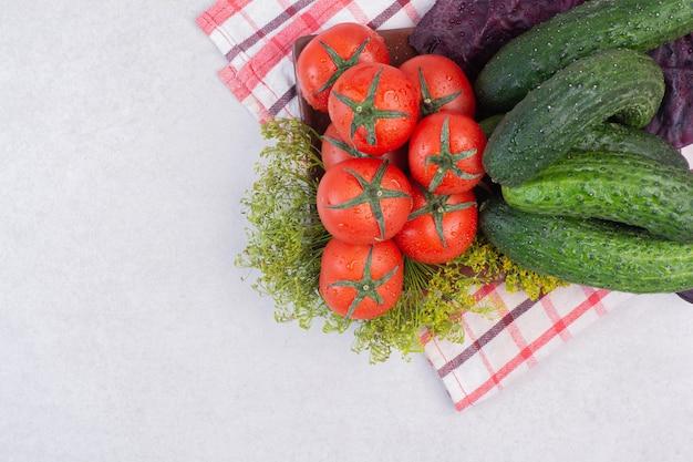 Ogórki, zielenie i pomidory na obrusie.