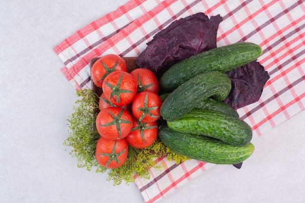 Ogórki, zielenina i pomidory na obrusie.