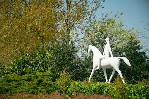 Ogród keukenhof, holandia - 20 kwietnia 2017: ludzie biały posąg na koniu w ogrodzie keukenhof w lisse, holandia.