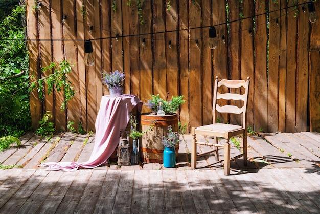 Ogród letni z drewnianą sceną i girlandą świateł