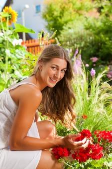 Ogród w lecie - szczęśliwa kobieta z kwiatami