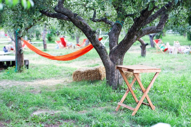 Ogród z hamakiem i drewnianym stołem do relaksu. taras, ogródek jabłkowy w lecie, drewniany stół ze stogiem siana. drewniany stół na patio w jesienny dzień we wsi. relaks w hamaku w ogrodzie.