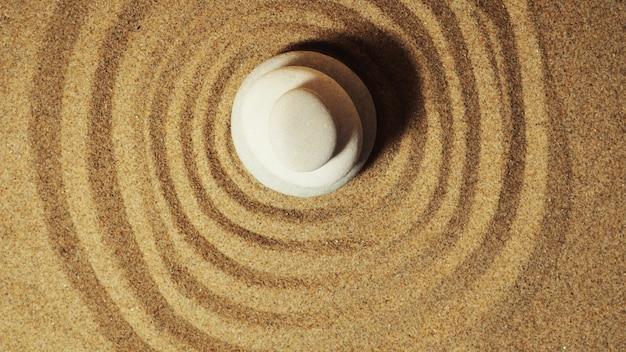 Ogród zen. piramidy białych i szarych kamieni zen na białym piasku z abstrakcyjnymi rysunkami fal.
