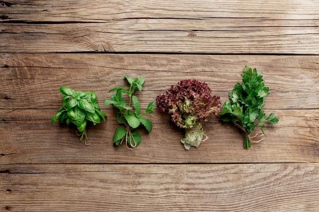 Ogrodnictwo i koncepcja zdrowego odżywiania z różnymi ziołami i liśćmi sałaty na drewnianym stole
