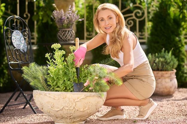 Ogrodnictwo, kopanie. pewna siebie, przyjazna kobieta w średnim wieku z łopatą ogrodową przykucnęła w pobliżu kwiatów w swoim ogrodzie w letni dzień