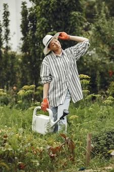 Ogrodnictwo latem. kobieta podlewania kwiatów konewką. dziewczyna w kapeluszu.