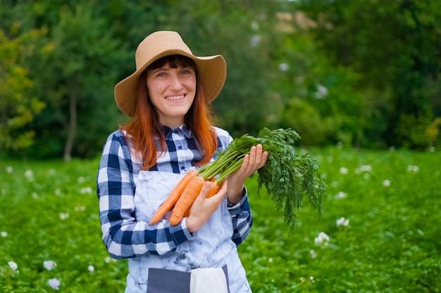 Ogrodnictwo - piękna młoda kobieta z organicznych marchewek w ogrodzie warzywnym. podświetlenie