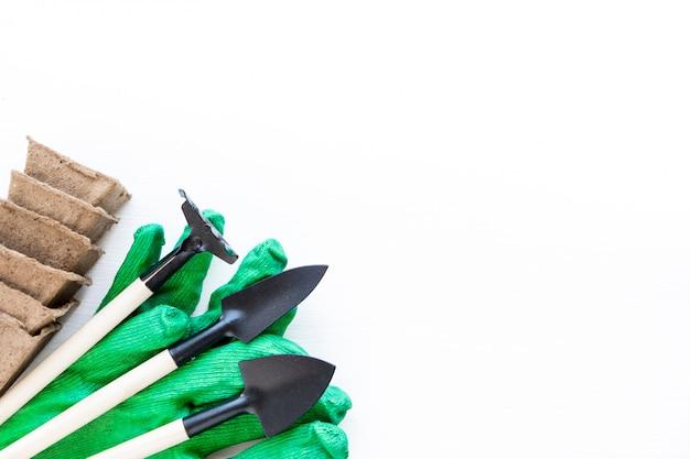 Ogrodnictwo w domu. uprawa żywności na parapecie. narzędzia, doniczki torfowe do sadzonek i rękawiczki rolnicze. copyspace dla tekstu, widok z góry. flatlay na białym tle drewnianych.