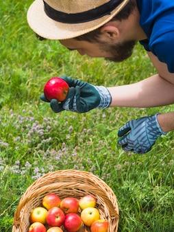 Ogrodniczka patrzeje świeżego czerwonego jabłka