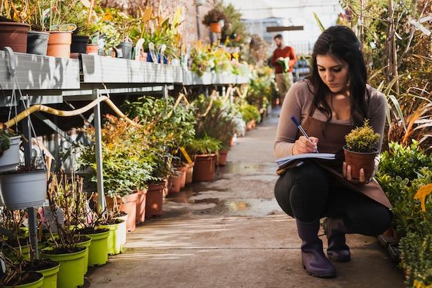 Ogrodniczka robić notatki o kwiacie