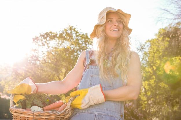 Ogrodniczki kobieta trzyma kosz warzywa w ogródzie