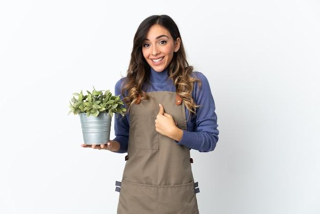 Ogrodnik dziewczyna trzyma roślinę na białym tle na białej ścianie z zaskoczeniem wyraz twarzy