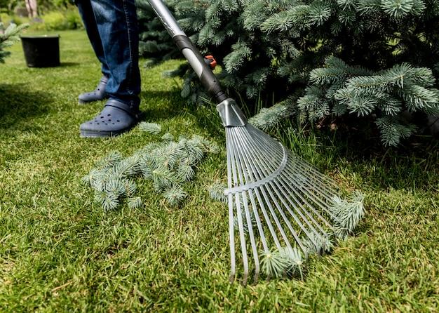 Ogrodnik grabienie cięcia liści w ogrodzie.