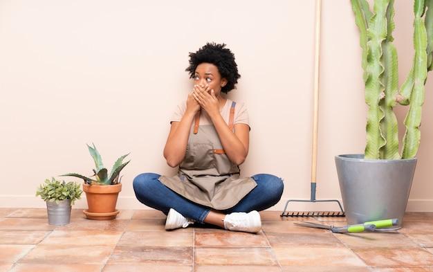Ogrodnik kobieta siedzi na podłodze wokół roślin