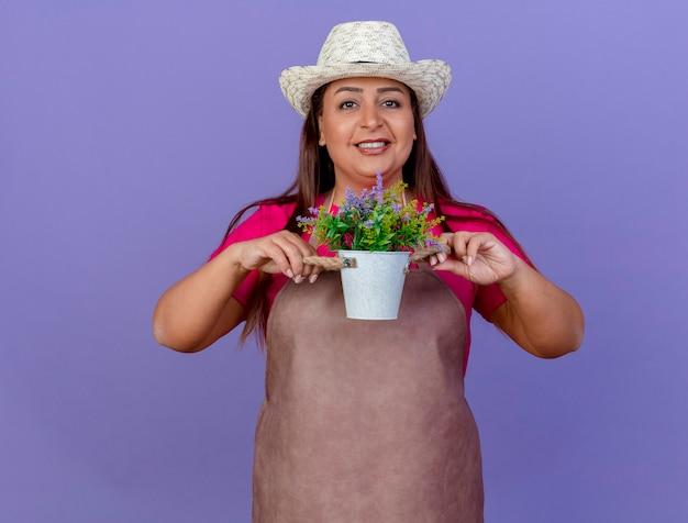 Ogrodnik kobieta w średnim wieku w fartuch i kapelusz pokazano roślin doniczkowych patrząc na kamery uśmiechnięty szczęśliwy twarz stojącą na fioletowym tle