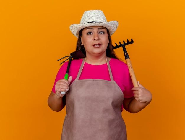 Ogrodnik kobieta w średnim wieku w fartuch i kapelusz, trzymając sutka i mini prowizji patrząc na kamery z poważną twarzą stojącą na pomarańczowym tle
