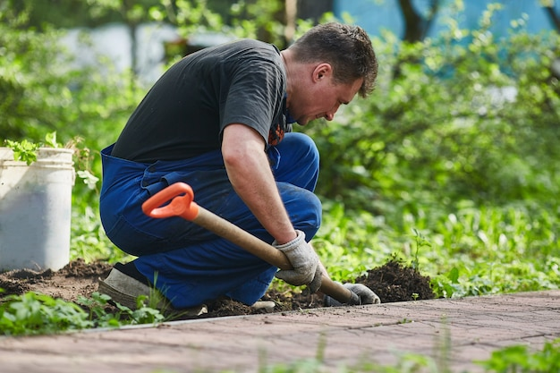 Ogrodnik kopie ziemię wiosną w ogrodzie. prace ogrodowe.