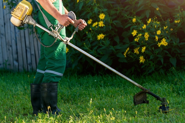 Ogrodnik kosi trawę za pomocą kosiarki.
