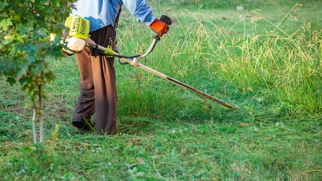 Ogrodnik koszący trawę kosiarką, pielęgnacja trawnika. natura.
