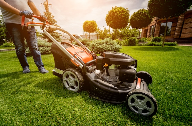 Ogrodnik koszenie trawnika. projektowanie krajobrazu. zielone tło