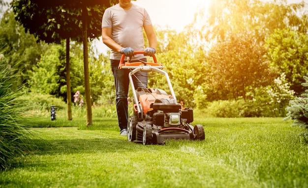 Ogrodnik koszenie trawnika. projektowanie krajobrazu.