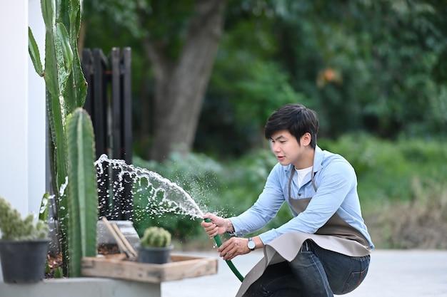 Ogrodnik mężczyzna podlewa roślinę w domu.