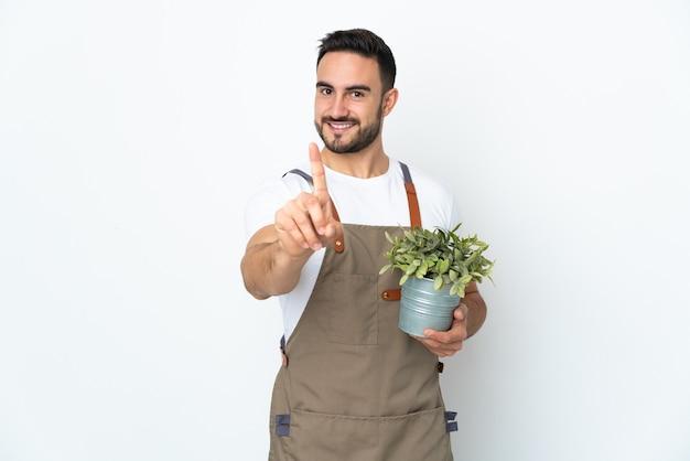 Ogrodnik mężczyzna trzyma roślinę na białym tle pokazując i podnosząc palec