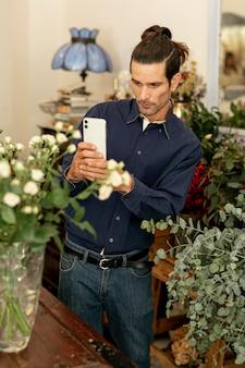 Ogrodnik mężczyzna z długimi włosami robienia zdjęcia