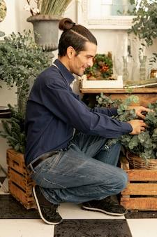 Ogrodnik mężczyzna z długimi włosami układający rośliny