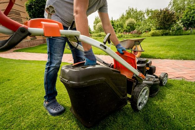 Ogrodnik opróżnia trawę kosiarki do taczki po koszeniu.