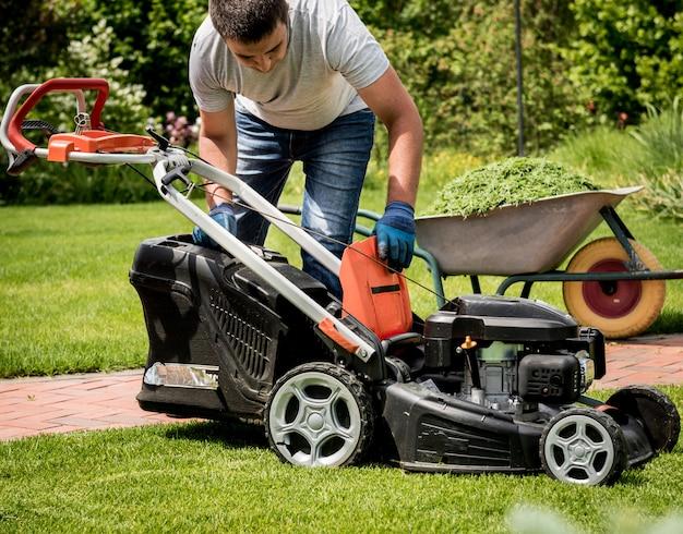 Ogrodnik opróżniający trawę z kosiarki do taczki po skoszeniu. projektowanie krajobrazu. prace ogrodowe