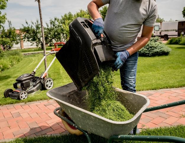 Ogrodnik opróżniający trawę z kosiarki do taczki po skoszeniu.